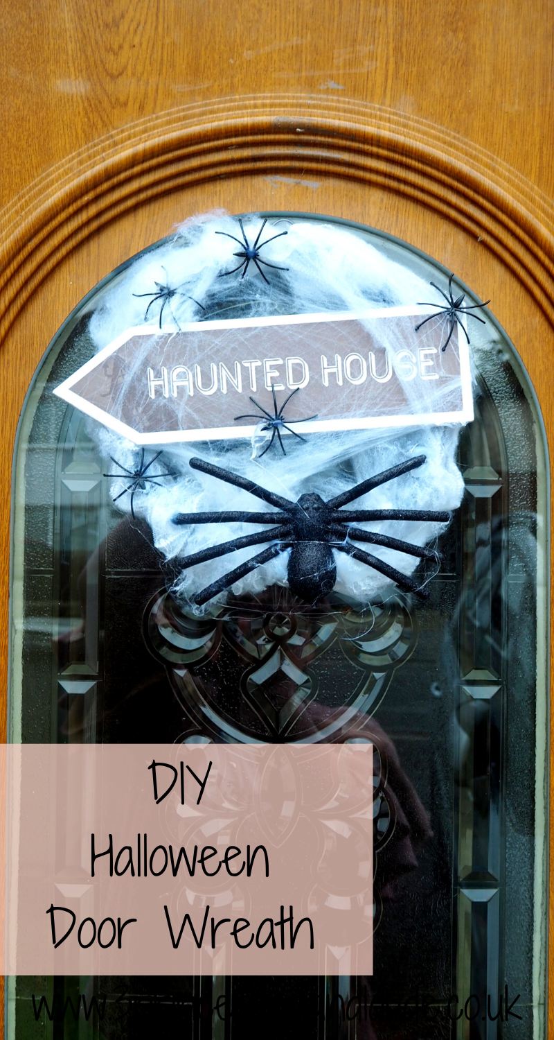 On a brown UPVC door, with a glass window hangs a circular door wreath with several small atrifical spiders scattered around, thick atrificial spider web, a large black glittered spider at the bottom of the wreath and across the middle pf the wreath is a wooden arrowed sign which says haunted house in white lettering