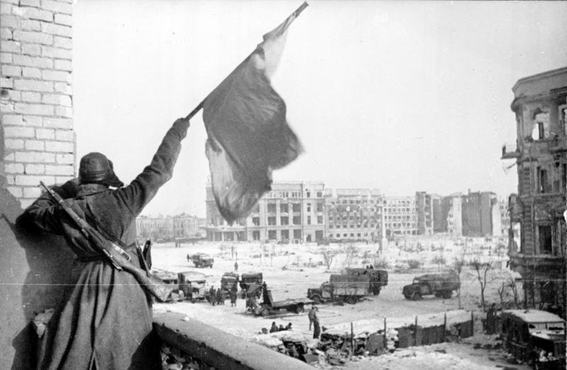 Soviet soldier waving the Red Banner over the central plaza of Stalingrad in 1943