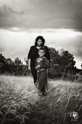 amazing black and white photo of a boy and his sister in a grassy meadow