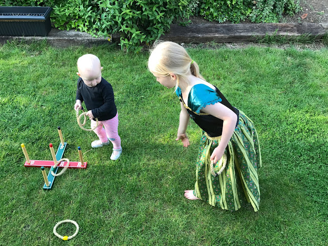 A big sister throwing a hoop while the little sister watches