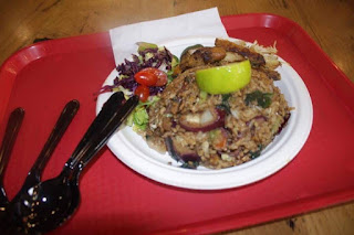 A heaping mound of brown fried rice with pieces of white egg with strips of white Chicken meat with a wedge of bright green lime on a red tray on a bright background.
