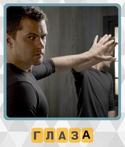 мужчина около зеркала с протянутой рукой и глаза 5 уровень в игре 600 слов