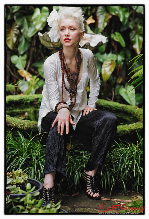 Model sitting on overgrown fountain in an old suburban garden. Fashion photographed by Kent Johnson, Sydney, Australia.