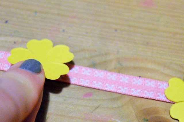 Paper flower being pressed to the ribbon.