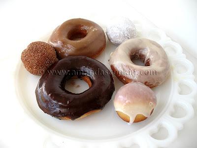 A photo of a plate of an assortment of homemade doughnuts.