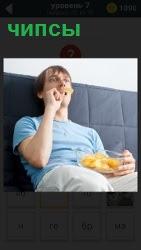 сидит мужчина на диване и ест чипсы из пакета