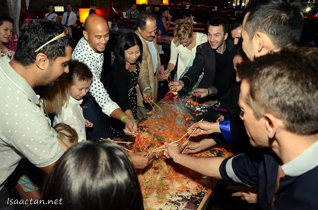 Guests having a great time tossing the yee sang for prosperity and luck