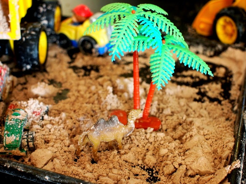 camel and palm tree in pretend dirt