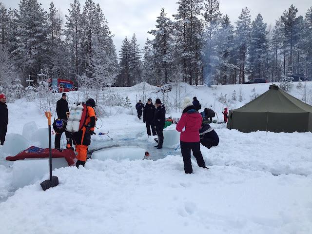 Sukeltaja ja muita ihmisiä avannon ympärillä jäällä, taustalla puolijoukkueteltta