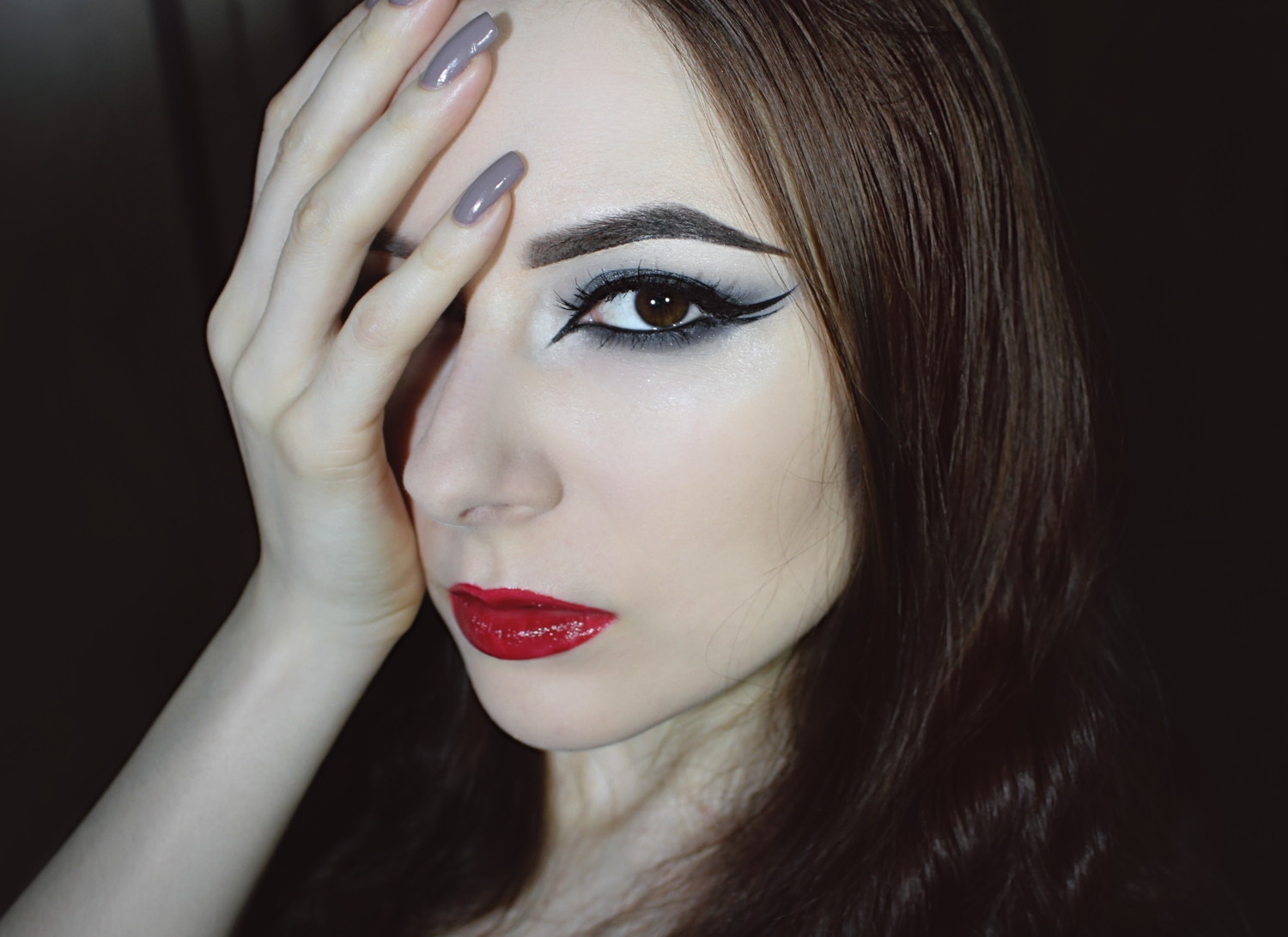 girl with smoky eye makeup, double eyeliner and red glossy lips is showing her makeup