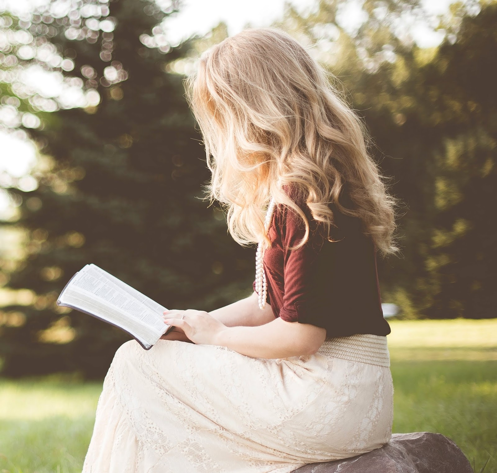 A blond woman sitting on a rock in a park, facing left, reading an book that's on her lap, with trees in the background