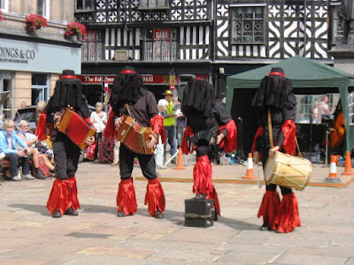 Four dancers in black and red with faces veiled in black