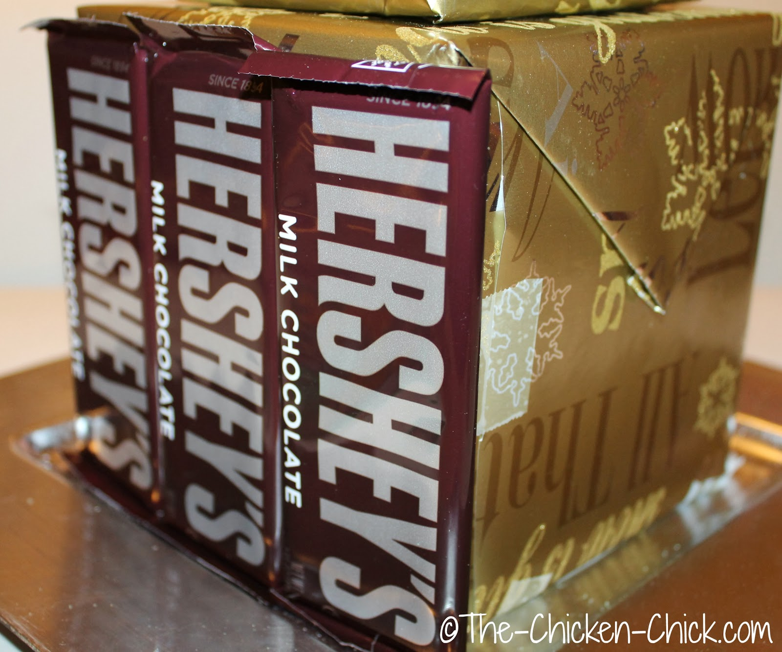 use double stick tape to back of candy bars and begin covering bottom of base box all the way around.