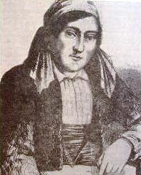 El bandolero, sentado, vestido con chaquetilla corta, fajín y pañuelo a la cabeza.