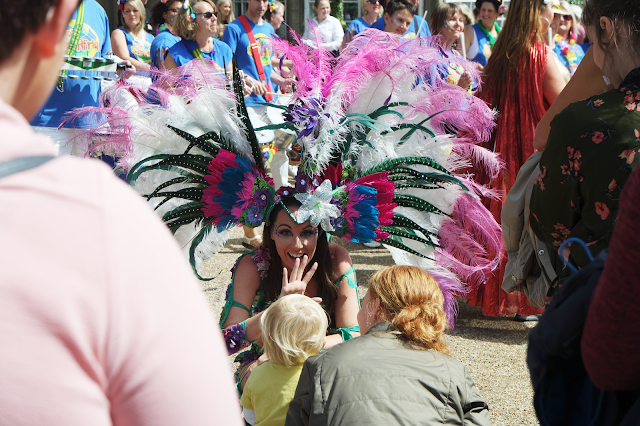 a dancer wearing face glitter and a pink feather headdress smiling and waving at a child in the crowd