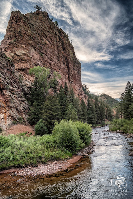 the Platte River flows around a bend, and a large rock formation in the Colorado mountains.