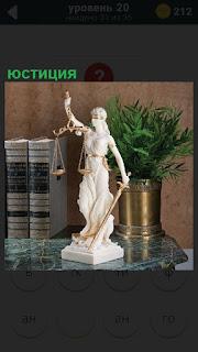 Скульптура юстиции и рядом стоят книги и ваза с зеленым растением