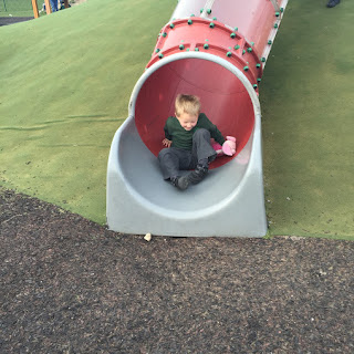 child on slide with soft toy