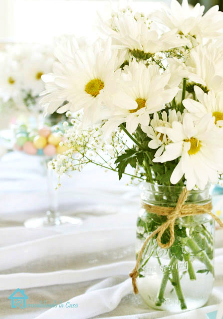 white and yellow flowers in clear mason jar