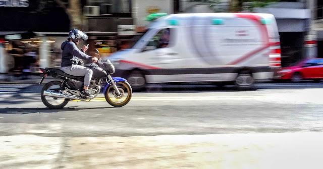 Motociclista viajando mirando su celular por avenida.en Bs.As.
