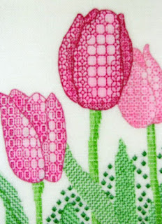 tulips stitched in the blackwork technique in which the density of the stitching pattern gives dimension to the shape of the subject
