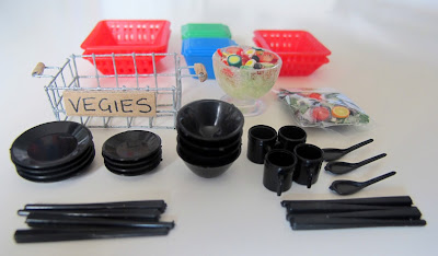 Selection of modern dolls' house miniature kitchen plasticware, and two salads: one in a bag, the other in a bowl.