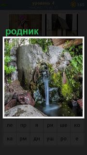 около камней в лесу течет родник в водоем, прозрачная вода