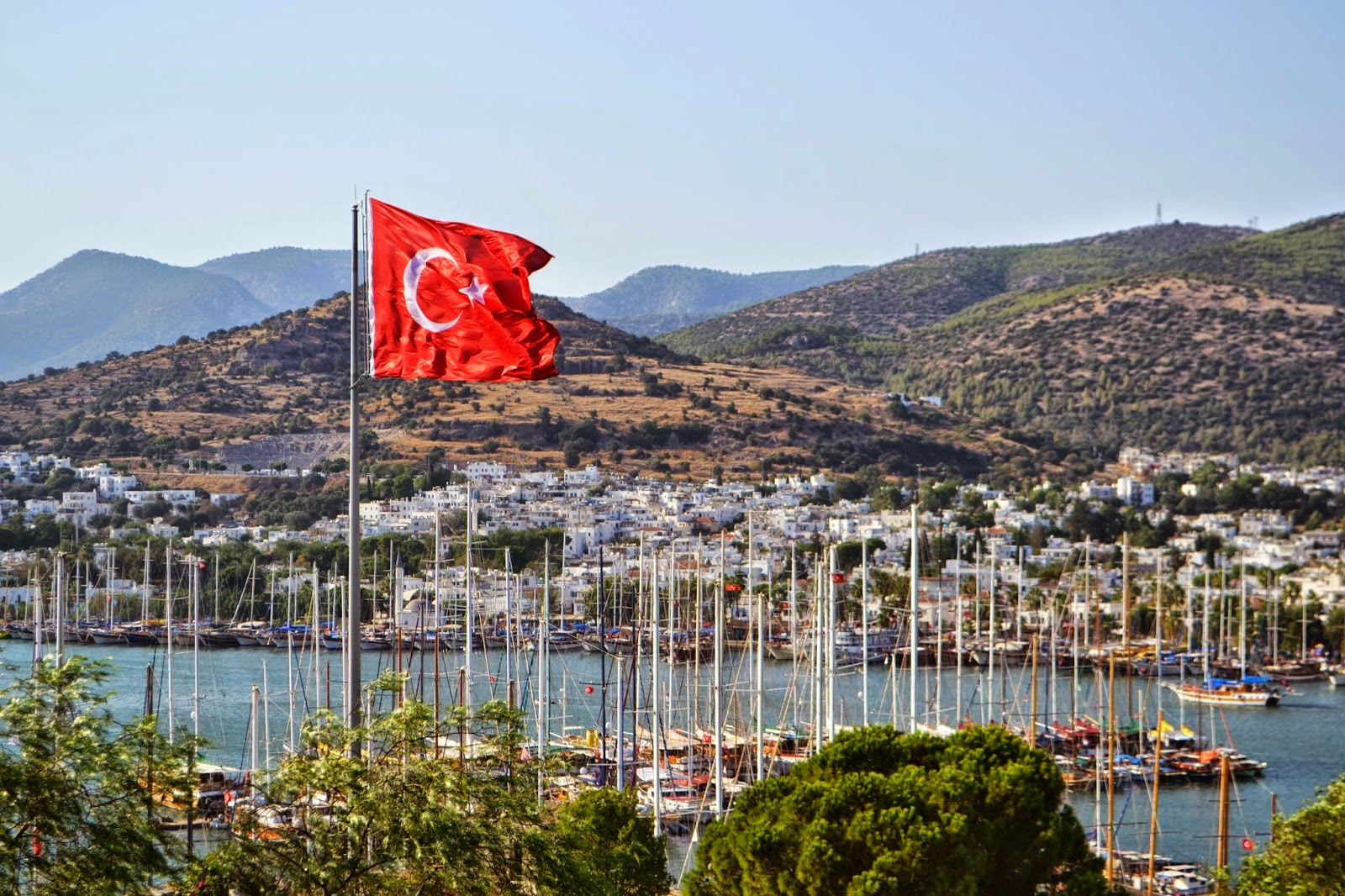 looking across the bay in Bodrum, Turkey. The Turkish flag can be seen in the foreground and behind that the bay filled with boats and the hillside covered in whitewashed houses.