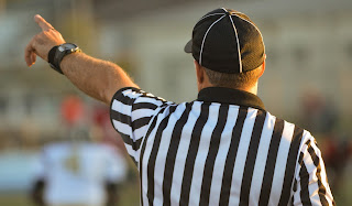 Referee Enforcing the Rules of the Game