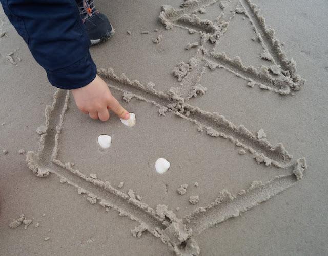 Drei einfache Strandspiele, für die Ihr nichts als Eure Hände braucht: Bilder im Sand zeichnen und mit Muscheln und Steinen verzieren