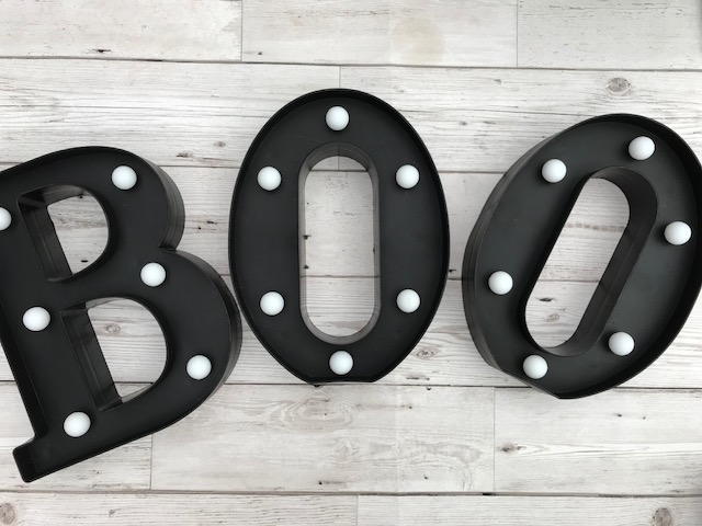 Plastic letters with small bulbs on the front, that spell BOO