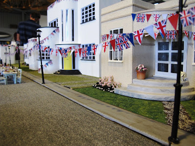 A row of Art Deco houses with british flag bunting strung between the lamp posts and chairs and tables set up for a street party.