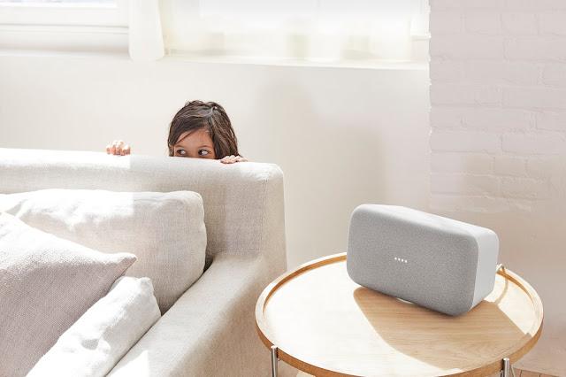 Ein Kind versteckt sich hinter einer Couch, daneben steht ein Google Home Max