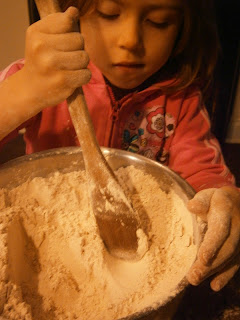 child stirs flour/batter