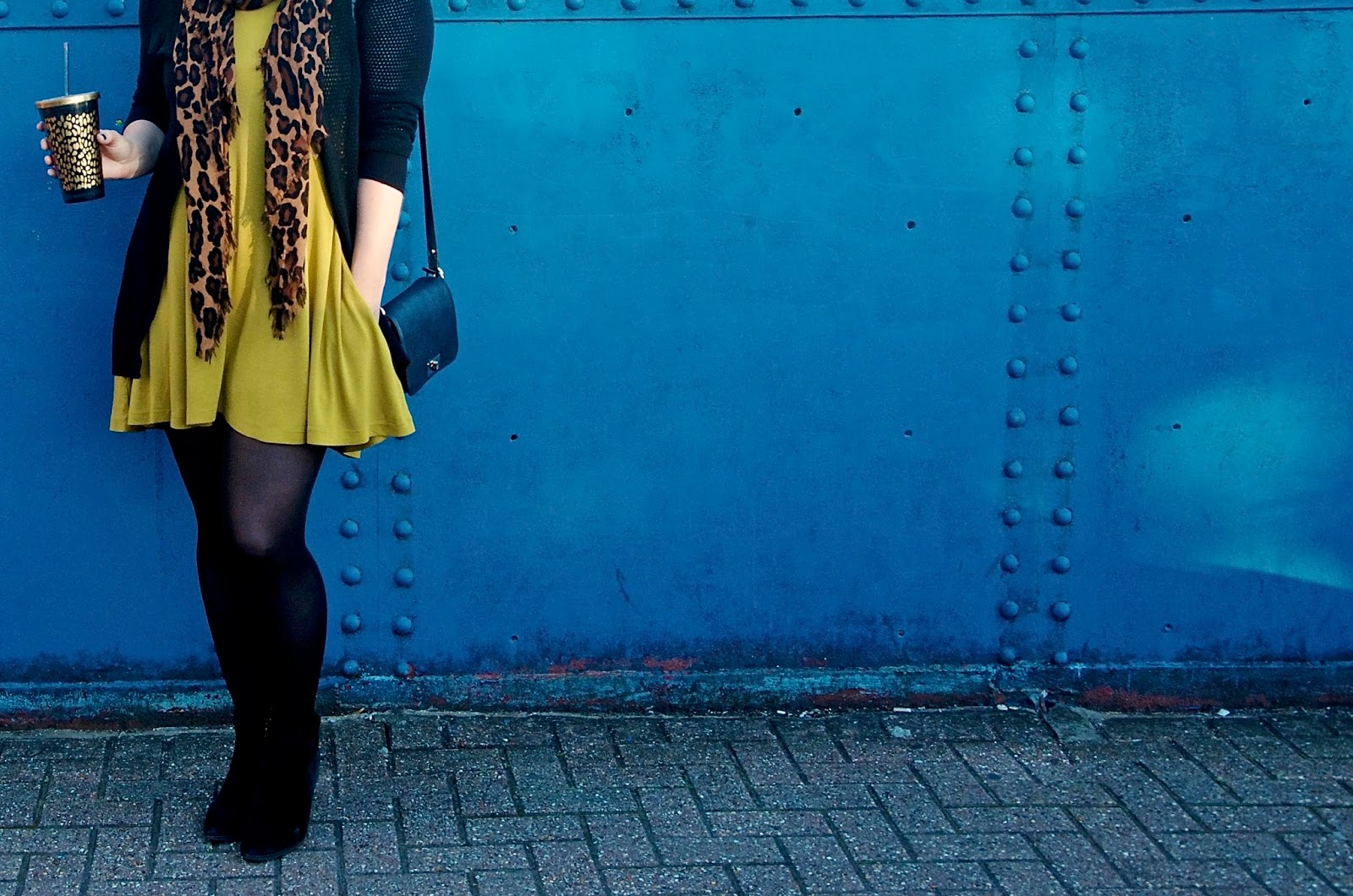 mustard yellow skater dress, leopard print scarf, black tights, black cardigan, leopard print tumbler