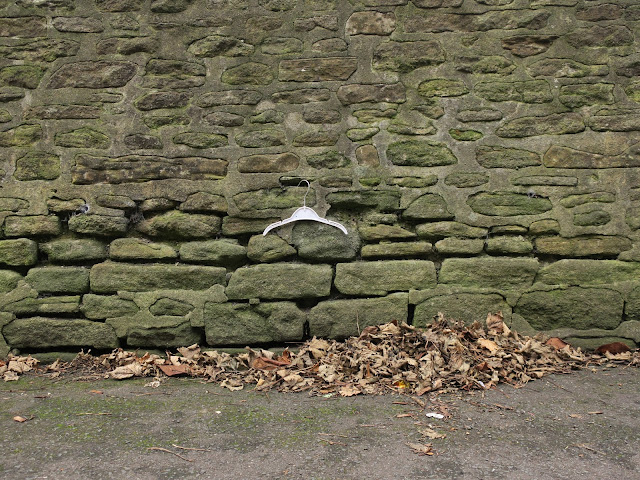 White plastic coat hanger hooked to a gap between stones on a wall above a pile of winter leaves.