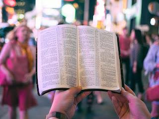 om cu o Biblie în mână - foto de Aaron Burden - unsplash.com