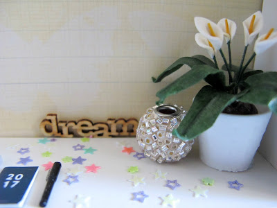 Close up of a one-twelfth scale modern miniature scene of a desk with a 2017 diary and pen, a peace lily and wooden word saying 'dream'.