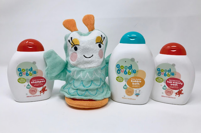 3 white bottles of bath products with red and blue lids and a bath mitt which looks like a bird or butterfly