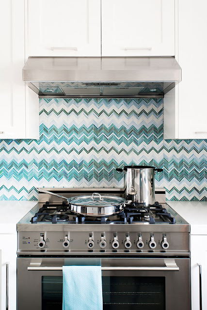 close up in blue and white zig zag chevron tiles, white cabinets and polished metal stove in a kitchen by Jute