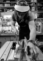 Image of a man wearing head protecting while using a circular saw table.