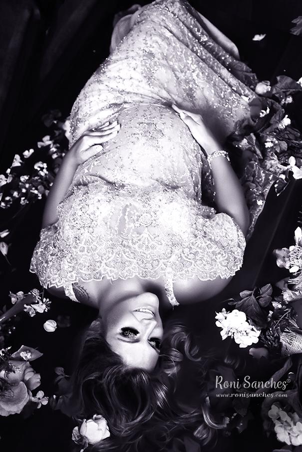 Book da gestante, foto de gravida com renda em pedraria deitada no chão coberto de flores