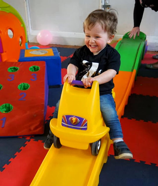 image shows a toddler riding on a small plastic roller coaster