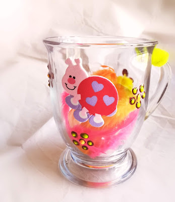 A decorated glass mug with light hue colors