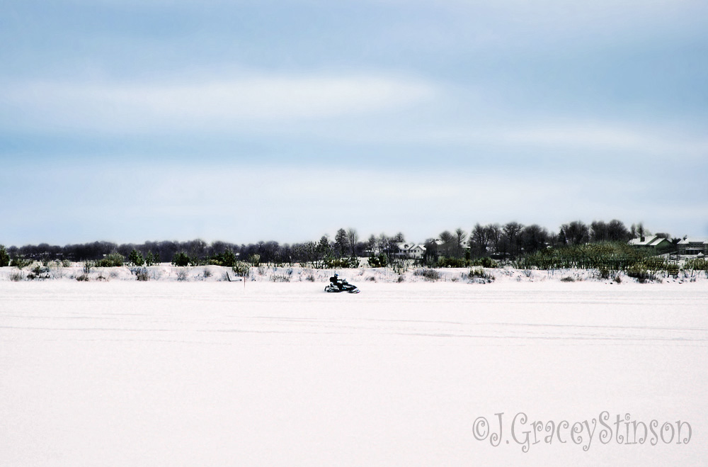 A snowmobile rider takes an early morning spin around a snow covered lake.