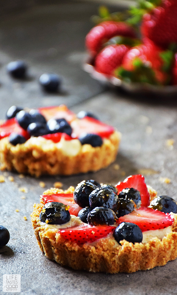 Red, White, and Blue Fruit Tart with a tray of strawberries in the background