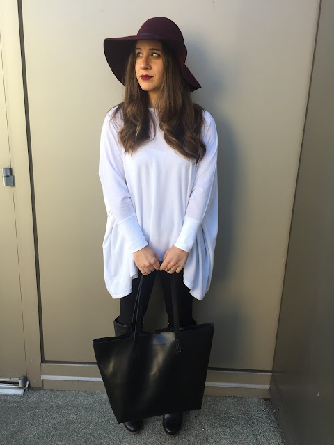 blogger looking to the side with burgundy wool floppy hat with white top, black leggings, black leather boots and black tote.
