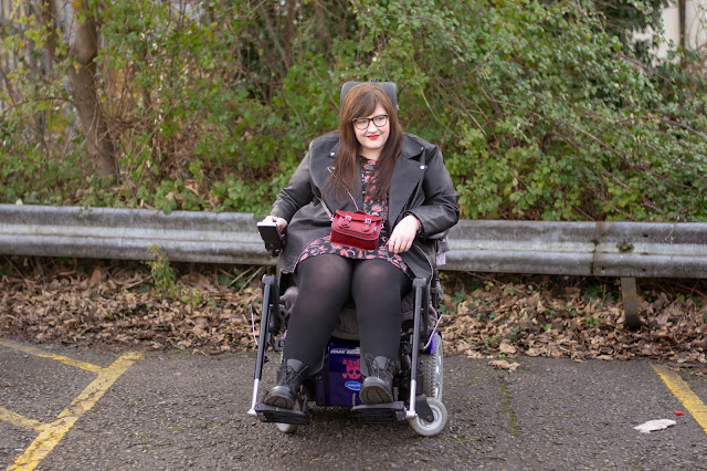 Plus size woman sat in powerchair wearing floral dress, black jacket, tights and Dr Martens