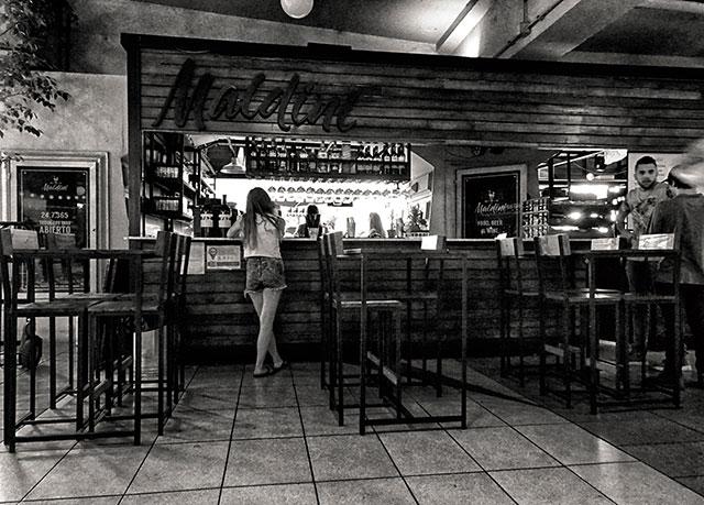 Interior en bar una chica enñla barra.
