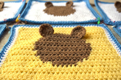 A close up of the centre square, yellow with a tan intarsia circle in the middle. The border is a row of white followed by a row of mid blue. There are two half-circle tan ears stitched to the top of the circle.  It is a low viewpoint from the bottom edge of the square so that the ears can be seen standing semi-upright above the surface of the yellow square which is surrounded on both sides and behind by similar white squares.